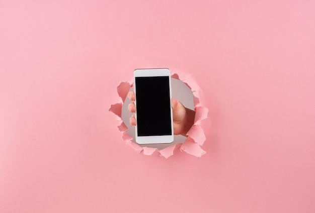 Frau, die smartphone in eingewickeltem loch im rosa hintergrund hält Premium Fotos