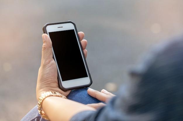 Frau, die smartphone mit dunklem schirm verwendet Premium Fotos