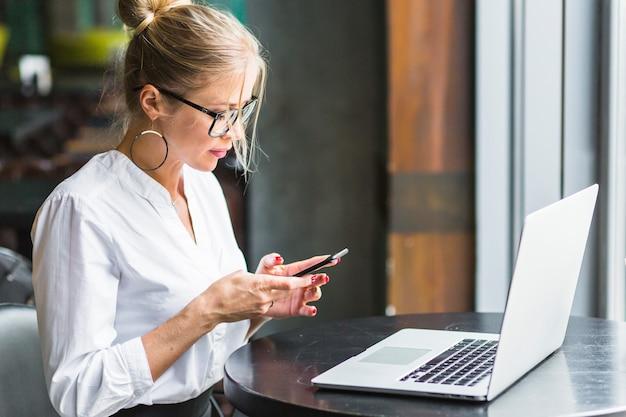 Frau, die smartphone mit laptop auf schreibtisch verwendet Kostenlose Fotos