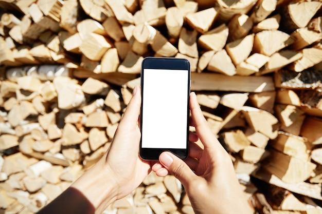 Frau, die smartphone mit leerem weißen bildschirm hält Kostenlose Fotos