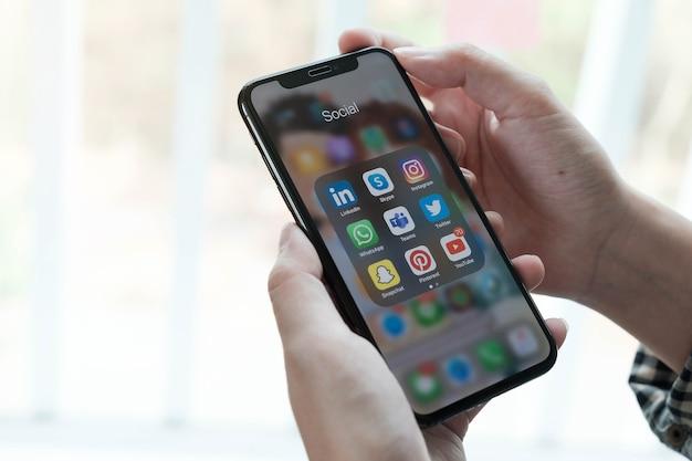 Frau, die smartphone mit symbolen der sozialen medien auf dem bildschirm verwendet Premium Fotos