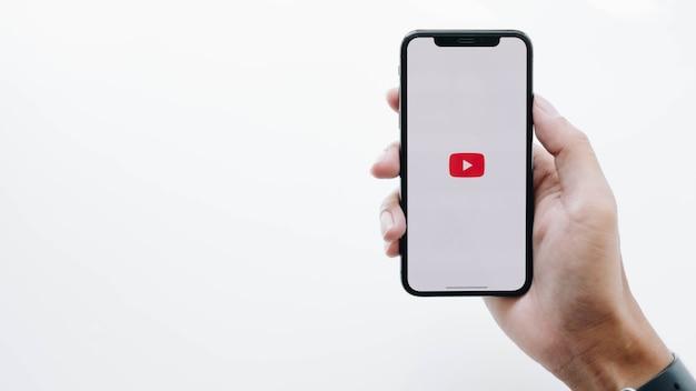 Frau, die smartphone mit youtube-app auf dem bildschirm hält Premium Fotos