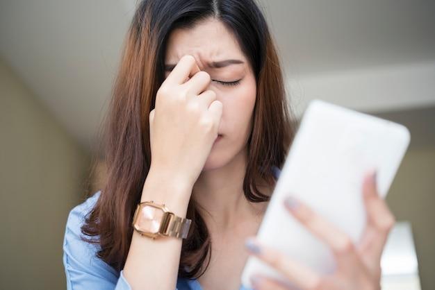 Frau, die smartphone verwendet und müdigkeit und kopfschmerzen glaubt. Premium Fotos
