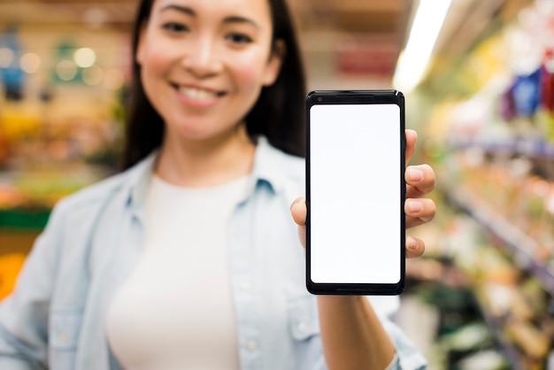 Frau, die smartphone zur kamera im gemischtwarenladen zeigt Kostenlose Fotos