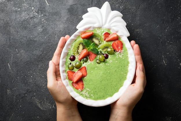 Frau, die smoothieschüssel mit kiwi, spinat, erdbeeren hält Premium Fotos