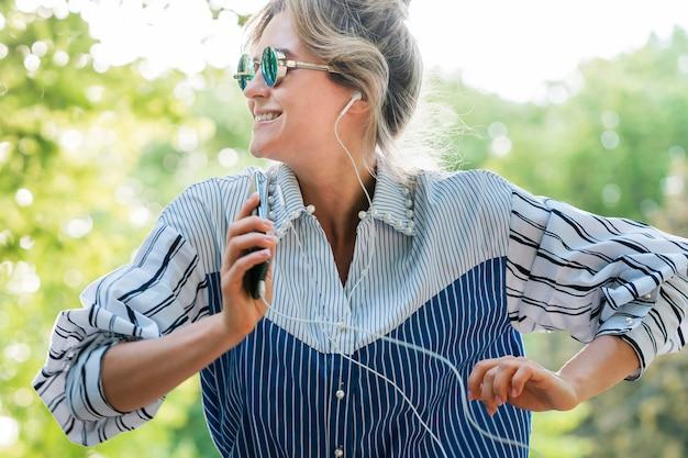 Frau, die sonnenbrille trägt und musik vorderansicht hört Kostenlose Fotos