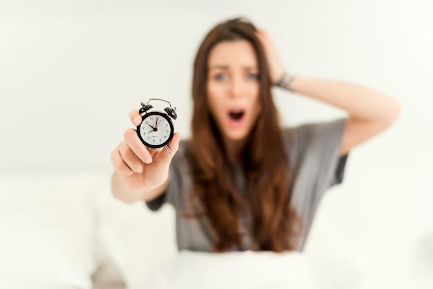 Frau, die spät für arbeit morgens mit wecker im fokus aufwacht Premium Fotos