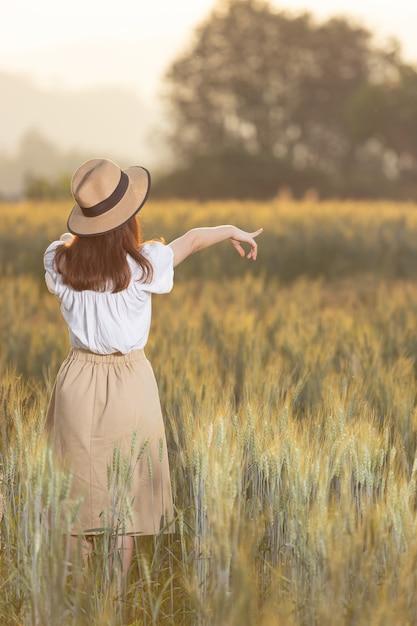 Frau, die spaß am gerstenfeld im sommer hat Premium Fotos