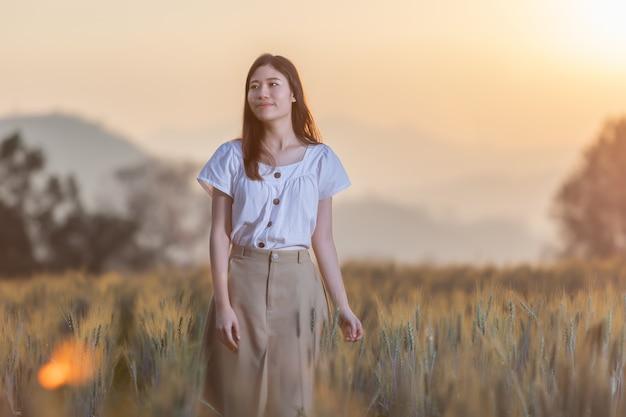 Frau, die spaß am gerstenfeld zur sonnenuntergangzeit hat Premium Fotos