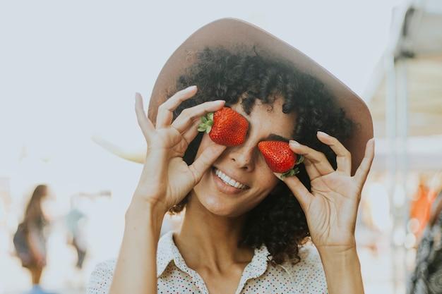 Frau, die spaß mit erdbeeren hat Kostenlose Fotos