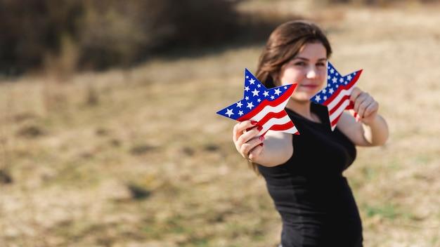 Frau, die sterne der amerikanischen flagge hält und kamera betrachtet Kostenlose Fotos