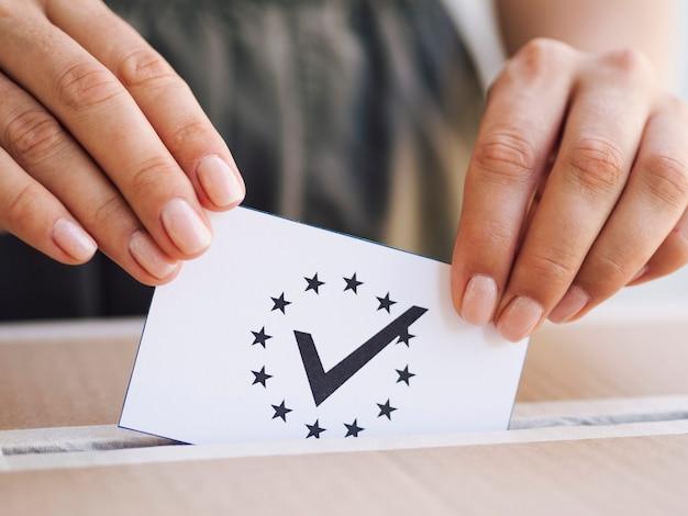 Frau, die stimmzettel in kastennahaufnahme legt Kostenlose Fotos
