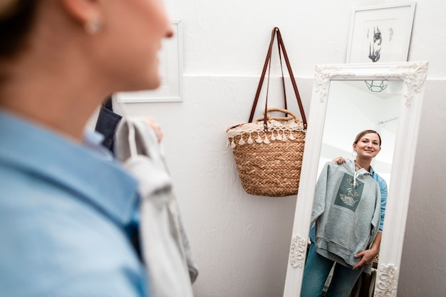 Frau, die t-shirt hält und im spiegel schaut Kostenlose Fotos