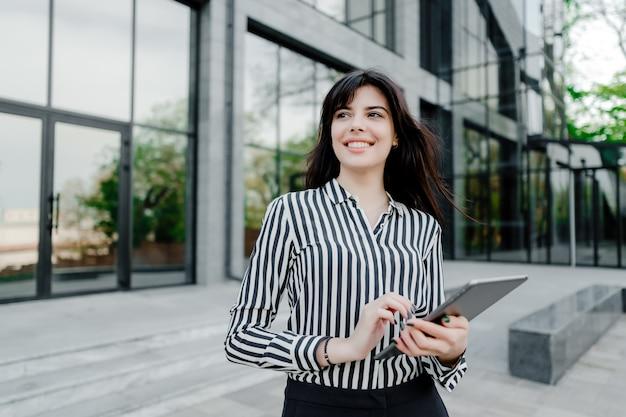 Frau, die tablette außerhalb des firmengebäudes verwendet Premium Fotos