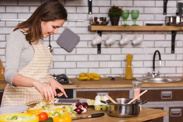 Frau, die tablette beim kochen des gemüses verwendet Kostenlose Fotos