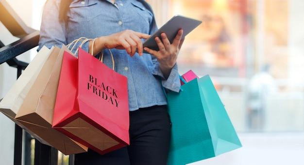 Frau, die tablette verwendet und black friday-einkaufstasche bei der stellung auf der treppe mit hält Premium Fotos