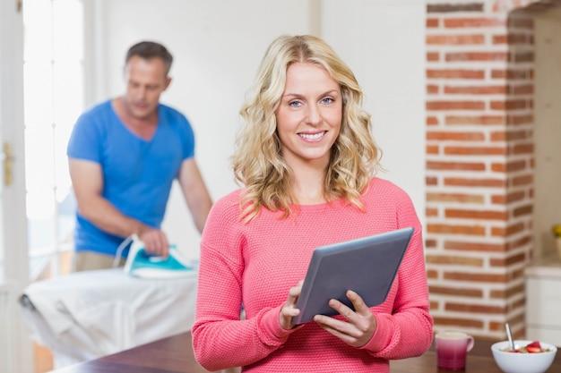 Frau, die tablette während ehemann verwendet eisen im wohnzimmer verwendet Premium Fotos