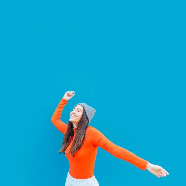 Frau, die tanz gegen blaue oberfläche genießt Kostenlose Fotos