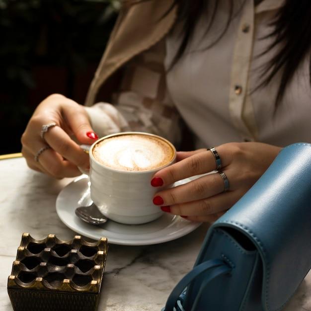 Frau, die tasse cappuccino hält Kostenlose Fotos
