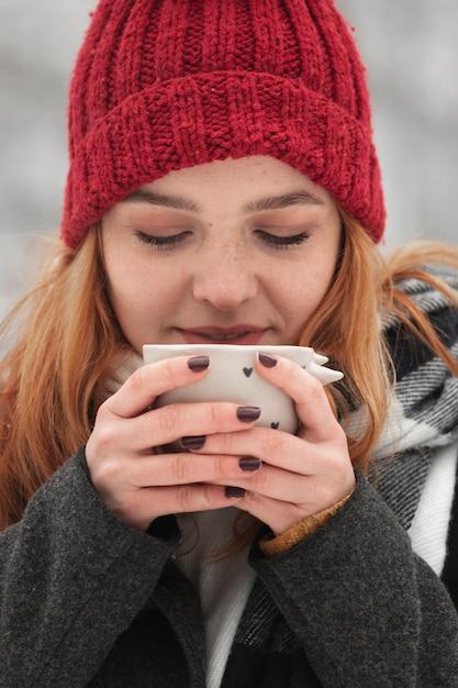 Frau, die tasse tee hält und einen schluck nimmt Kostenlose Fotos