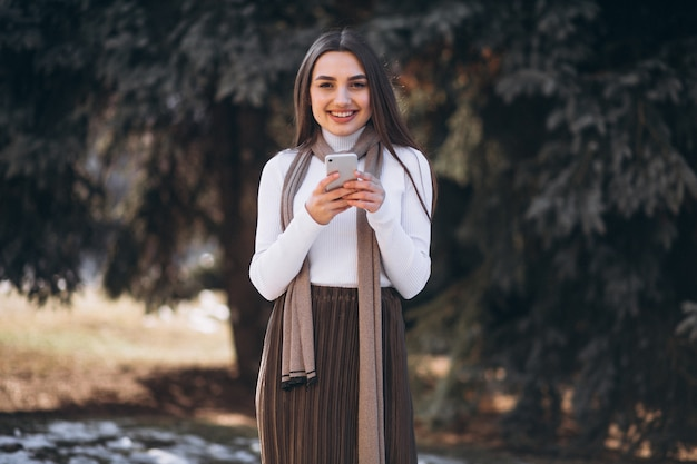 Frau, die telefon außerhalb der straße verwendet Kostenlose Fotos