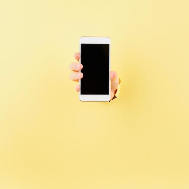 Frau, die telefon in eingewickeltem loch im rosa hintergrund hält Premium Fotos