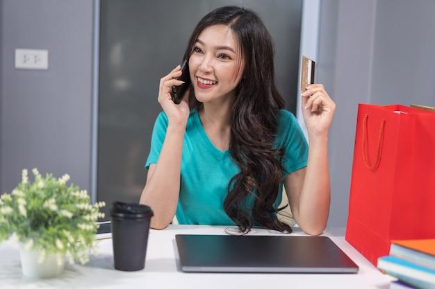 Frau, die telefonisch telefoniert und kreditkarte zum on-line-einkaufen hält Premium Fotos