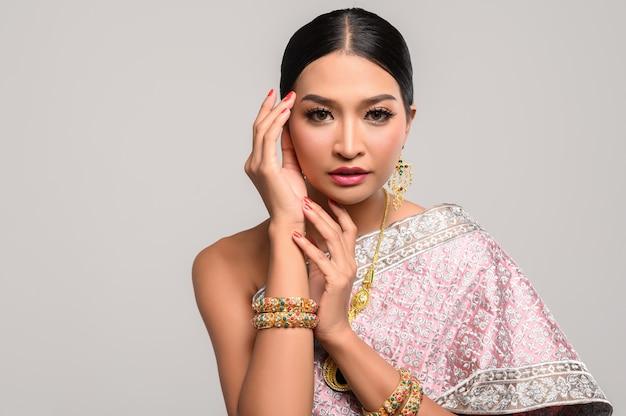 Frau, die thailändische kleidung und hände berühren den kopf trägt. Kostenlose Fotos