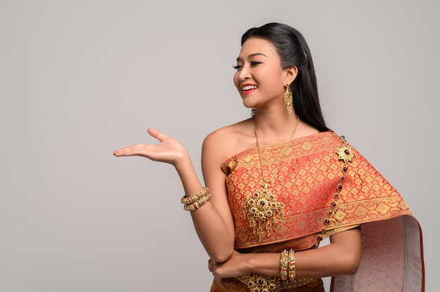 Frau, die thailändisches kleid trägt, das ein handsymbol machte Kostenlose Fotos