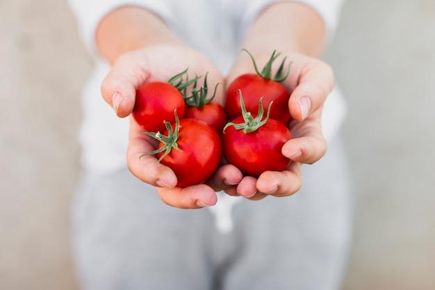 Frau, die tomaten in ihren händen hält Kostenlose Fotos