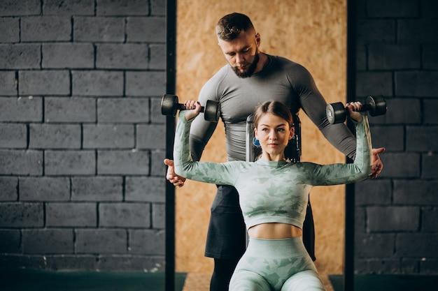 Frau, die training im fitnessstudio mit trainer macht Kostenlose Fotos