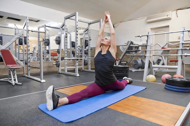 Frau, die training in der turnhalle, übendes yoga der frau ausdehnend tut Premium Fotos