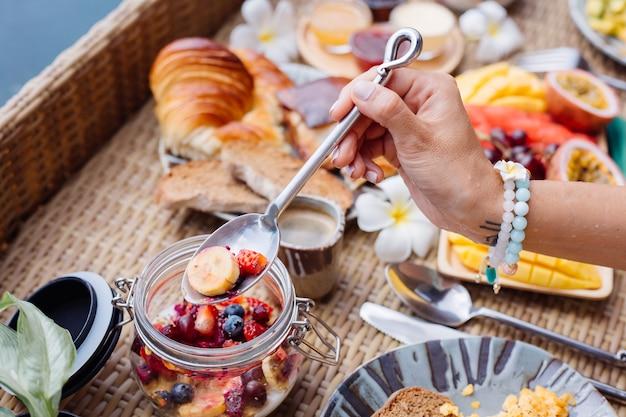 Frau, die tropisches gesundes frühstück an der villa auf schwimmendem tisch hat Kostenlose Fotos