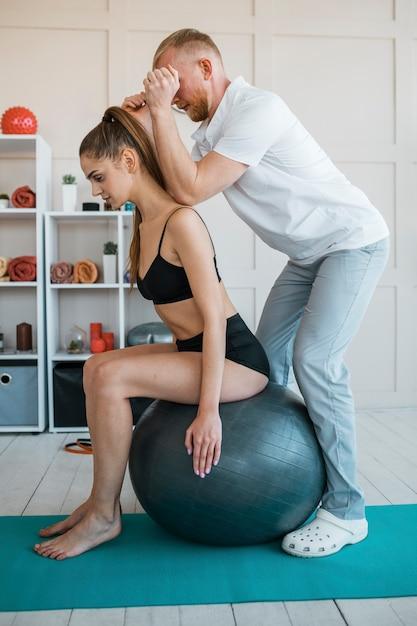 Frau, die übungen mit ball und männlichem physiotherapeuten macht Kostenlose Fotos