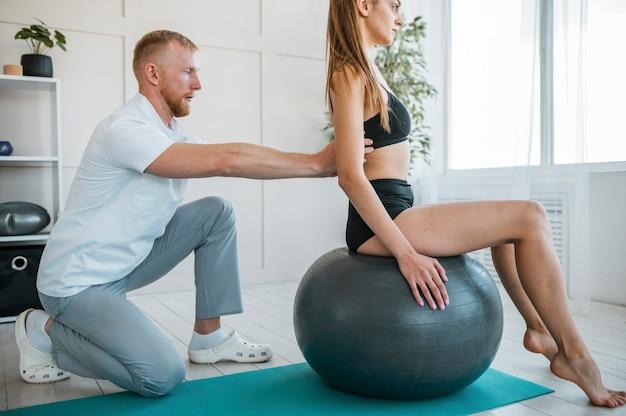 Frau, die übungen mit ball und physiotherapeut macht Kostenlose Fotos