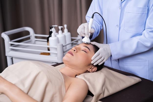 Frau, die ultraschallgesichtsschönheitsbehandlungs-hautpflege empfängt Premium Fotos