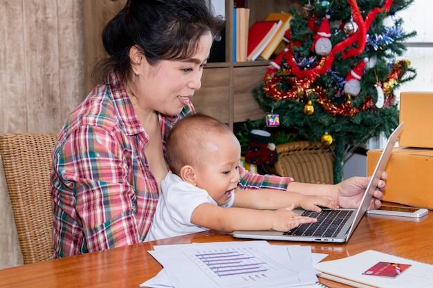 Frau, die um ihrem baby beim arbeiten im büro nahe dem weihnachtsbaum sich kümmert Premium Fotos