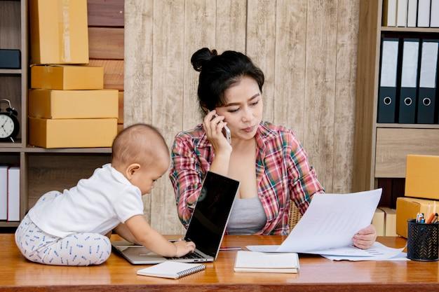 Frau, die um ihrem baby beim arbeiten im büro sich kümmert Premium Fotos