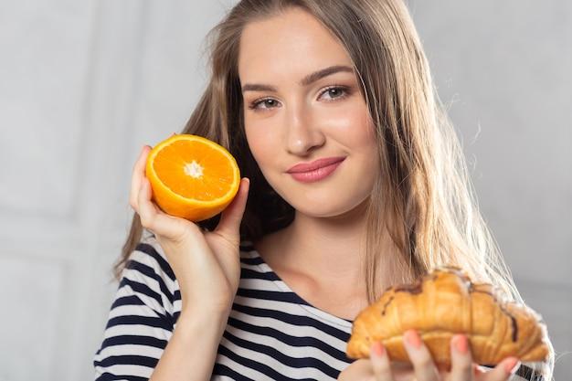 Frau, die ungesunden kuchen und orange frucht vergleicht Premium Fotos