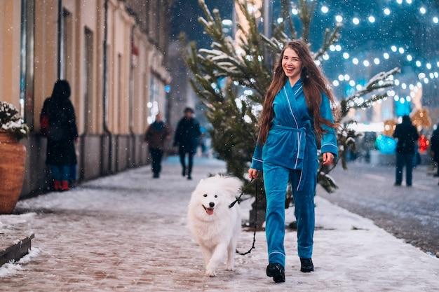 Frau, die unten mit weißem hund geht Kostenlose Fotos