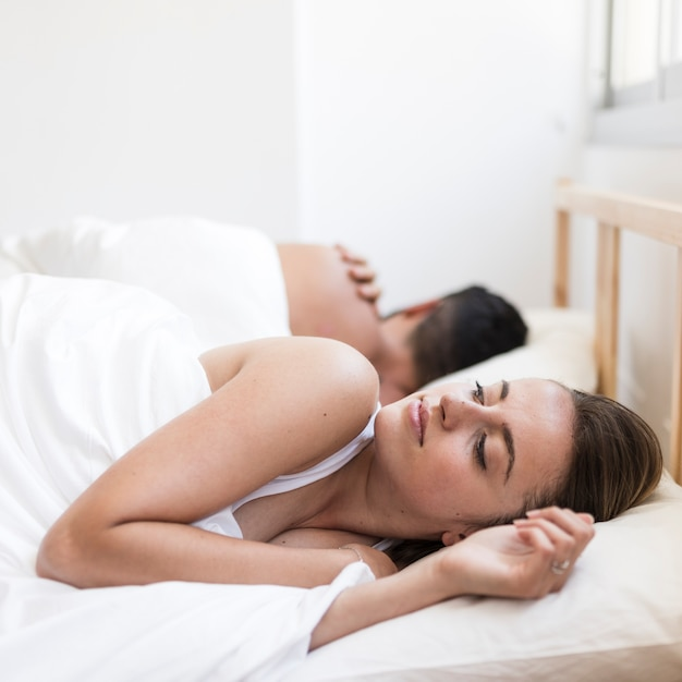 Frau, die unter der schlaflosigkeit liegt auf bett nahe ihrem ehemann leidet Kostenlose Fotos