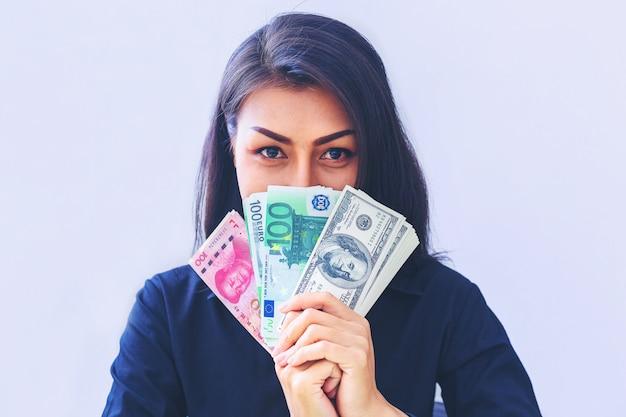 Frau, die usd-dollar, yuan rmb, eurogeldwahl und denken an geschäft hält Premium Fotos