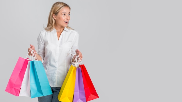 Frau, die viele bunte einkaufstaschen mit kopienraum hält Kostenlose Fotos
