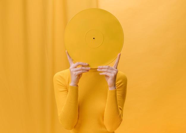 Frau, die vinyl vor gesicht in einer gelben szene hält Kostenlose Fotos