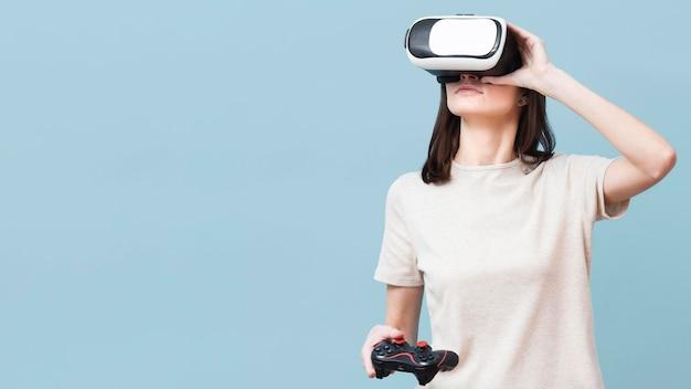 Frau, die virtual-reality-headset trägt und fernbedienung hält Kostenlose Fotos