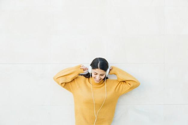 Frau, die vor hörender musik der wand auf kopfhörern steht Kostenlose Fotos