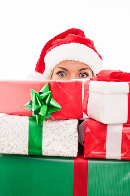 Frau, die weihnachtsgeschenk vor gesicht hält Kostenlose Fotos