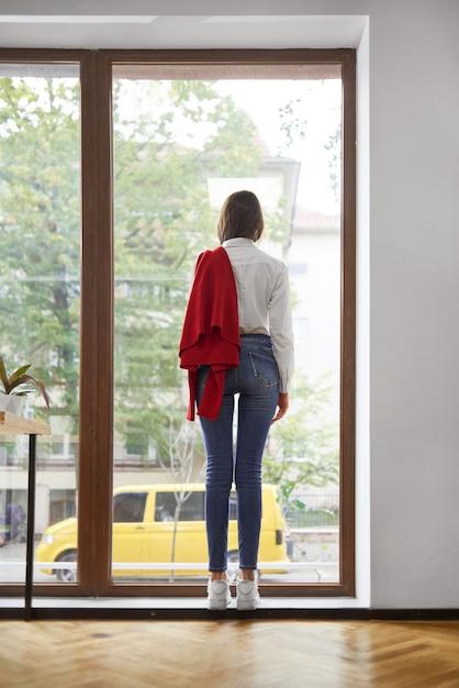 Frau, die weißes hemd und blaue jeans trägt, die nahe dem fenster stehen Premium Fotos