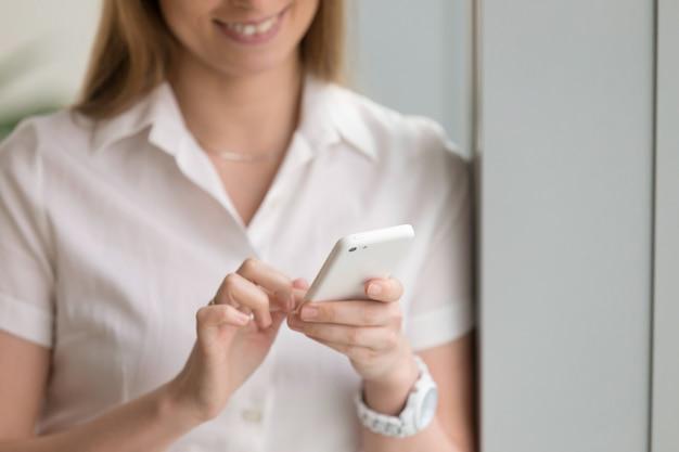 Frau, die weißes telefon, weibliche hände unter verwendung des smartphone, abschluss hochhält Kostenlose Fotos