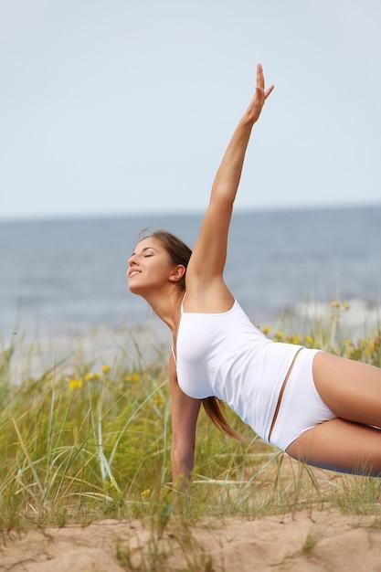 Frau, die yoga am strand macht Kostenlose Fotos